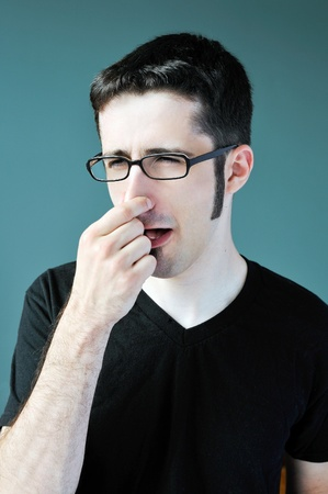 A young man blocks his nose after smelling something bad. photo