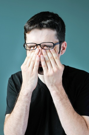 A young man pushing his glasses up and rubbing his eyes. Stock Photo