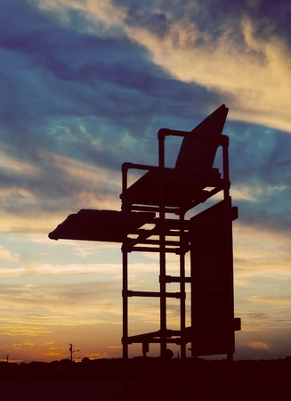 A lifeguard tower silhouette against a sunset sky. photo
