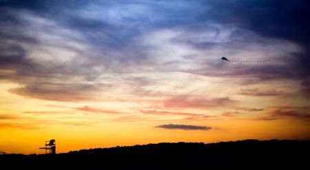 A lifeguard tower silhouette and flying kite against a sunset sky.
