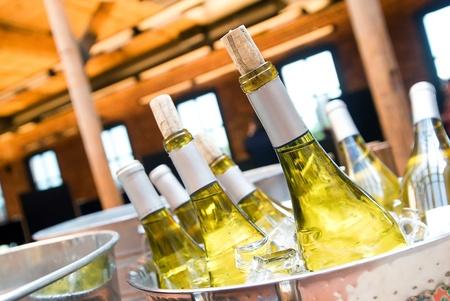 Flessen witte wijn op het ijs op een feestje.