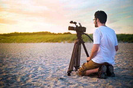 A videographer documenting a sunset on the beach.