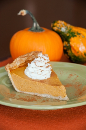 A piece of pumpkin pie on a green plate. Stock Photo