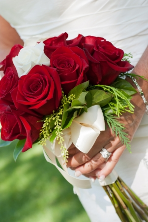 Close up of a bride holding a wedding bouquet with red and white roses. Stock Photo