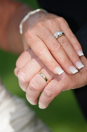 Newlywed bride and grooms hands showing their wedding rings.