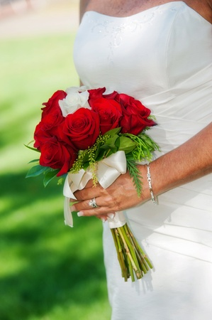 빨간색과 흰색 장미 결혼식 꽃다발을 들고 신부 닫습니다.