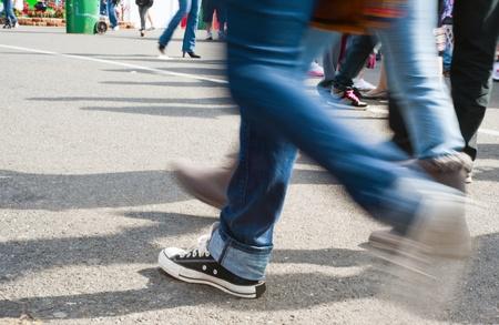 スニーカー: ぼやけた足コンクリート舗装の上を歩いてします。