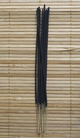 Dark inscense on bamboo background