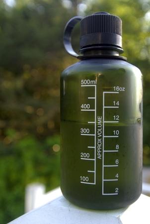 reusable: Un duro, verde, plastica, bottiglia riutilizzabile d'acqua circondato da piante verdi