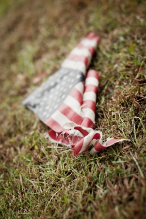 tattered: A tattered and torn American flag on the ground  Stock Photo