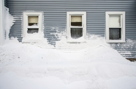 A huge snow mound piled under three residential windows in the aftermath of the Blizzard of 2013 in Worcester, Massachusetts. photo