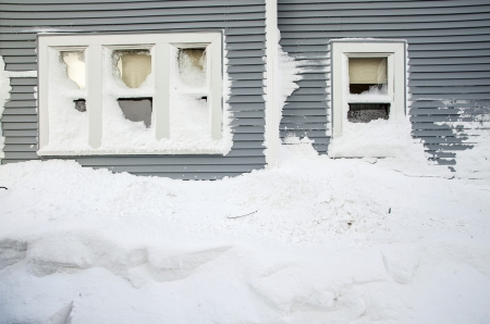 A huge snow mound piled under residential windows in the aftermath of the Blizzard of 2013 in Worcester, Massachusetts. Stock Photo - 17898497