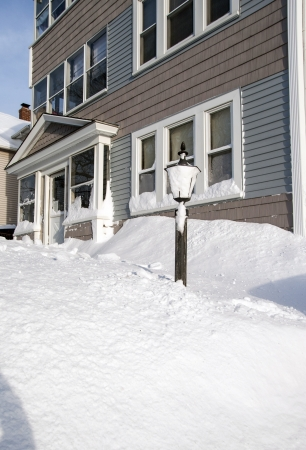 The aftermath of the blizzard of 2013 leaves 28 inches of snow piled up around this light pole in front of a residential home. Stock Photo