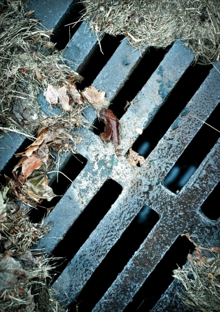An abstract rusty sewer grate with wet autumn leaves and debris.