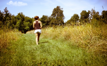 A young woman walking away along a nature path  photo