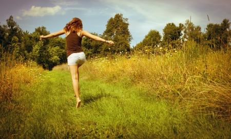 Back of young woman skipping down nature walk way