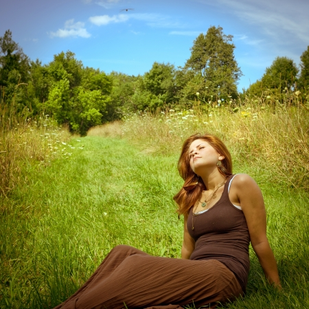 Young brunette woman relaxing in a sunny field photo