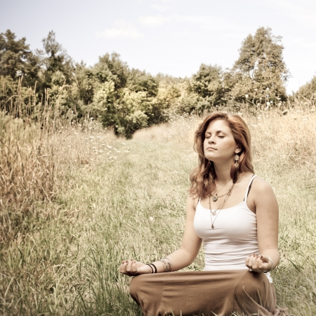 Young woman in lotus position in a sunny field photo