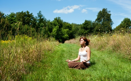 ohm: Young woman in lotus position meditating in nature