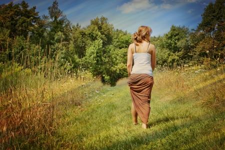 parejas caminando: Una mujer joven se alejaba por un sendero naturaleza Foto de archivo