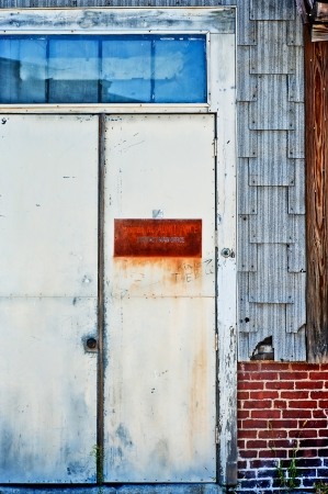 unsightly: Dilipidated old metal door to an industrial building. Stock Photo