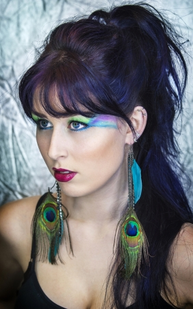 piercing: Beautiful young woman in peacock inspired makeup.