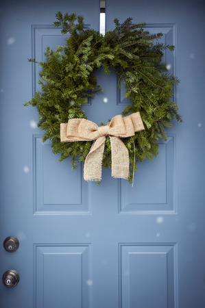 front of: Festive holiday wreath hanging on a blue door Stock Photo