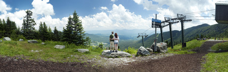 A young couple looks out over a panoramic view from Mount Mansfield in Vermont, USA   photo