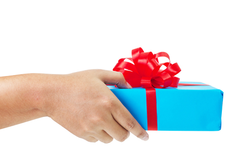 Asian hand giving a gift wrapped in blue box with red ribbon and bow. the most beautiful gift isolated on white background