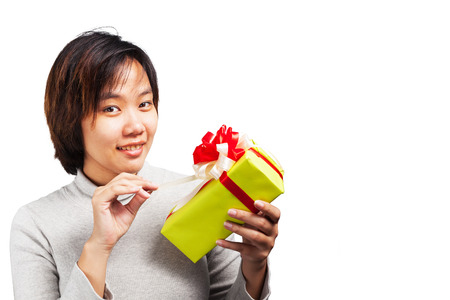 unwrapping: Asian female unwrapping her gifts with happiness over white background Stock Photo