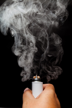 activating: Electronic Cigarette or vaper is activating and release a cloud in a human hand, black color background Stock Photo