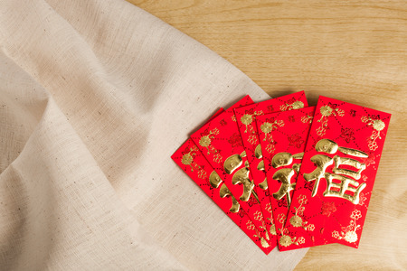 Chinese New Year Decorations red envelope on wood and gunny sack (Foreign text means fortune