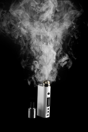 activating: Electronic Cigarette or vaper is activating and release a cloud, black color background Stock Photo