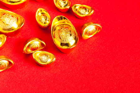 fortunate: Chinese Gold ingot (Sycees, YuanBao ) are used a symbol of prosperity among Chinese people. representing a fortunate year to come. On red color background with copy space and ready to use.
