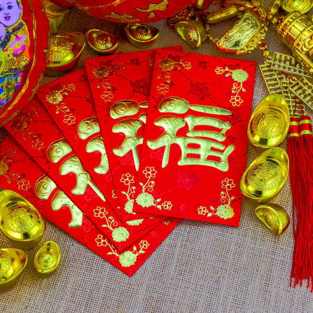 Chinese new year ornament on gunny sack, red envelope with Chinese letter FU meaning meaning fortune or good luck, gold ingot, Chinese lamp Stock Photo