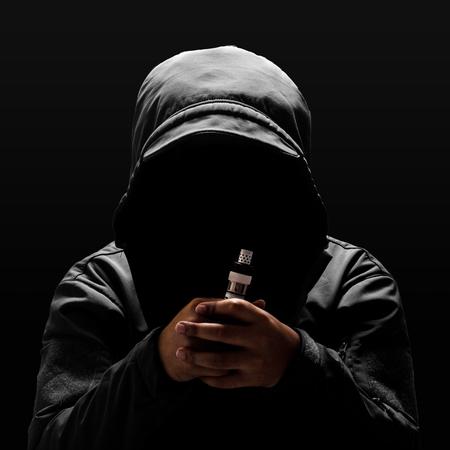unrecognizable person: Unrecognizable person, Unrecognizable person wearing hood, holding electronic cigarette  black color background