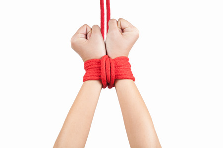 tied up: Hands of a missing kidnapped, abused, hostage, victim woman tied up with rope in emotional stress and pain, afraid, restricted, trapped, call for help, struggle, terrified.