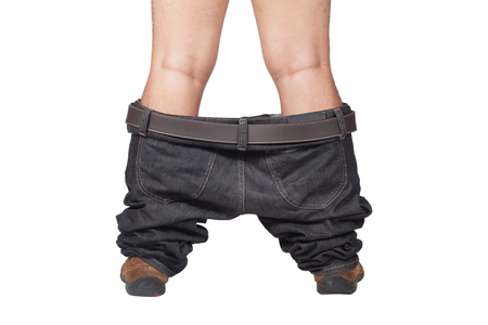 Caught with your pants down - man in brown shoes and jeans dropped down standing on floor, isolate on white background Stock Photo