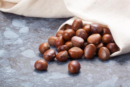 castaas: Imagen horizontal de un montón de castañas en el suelo de piedra de la textura con copia espacio