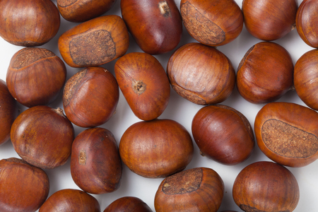 casta�as: Group of grilled chestnuts. On white background. Autumn background. Foto de archivo