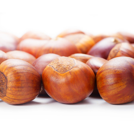 castaas: Group of grilled chestnuts. Isolate on white background. Autumn background.