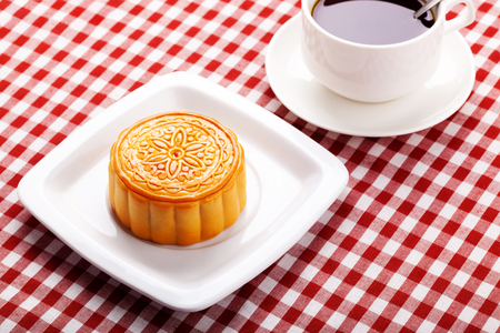 Chinese mid autumn festival foods. Traditional mooncakes on table setting with cup. photo & Chinese Mid Autumn Moon Cake Festival Foods. Traditional Chinese ...