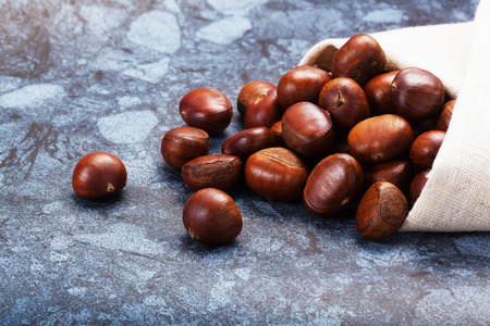 castaas: Horizontal image of a pile of chestnuts on stone texture floor with copy space