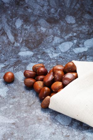 castaÑas: Imagen horizontal de un montón de castañas en el suelo de piedra de la textura con copia espacio