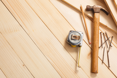 old items: carpentry tools on wooden background, top view. Empty space for Your text in the left side.