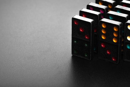 sabotage: Black color dominoes with colorful dot game pieces lying on dark background Stock Photo