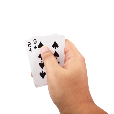 Close up of man hand holding a poker cards isolated on white background with clipping path