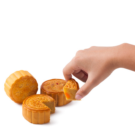 hand pick up a slice of moon cake on isolated white background with clipping path copy space