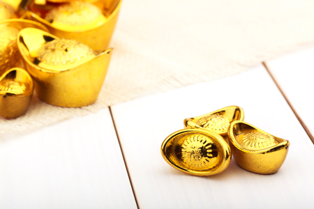 Gold Chinese ingot (Yuan Bao) on wooden white background with copy space - best for Chinese New Year use Stock Photo