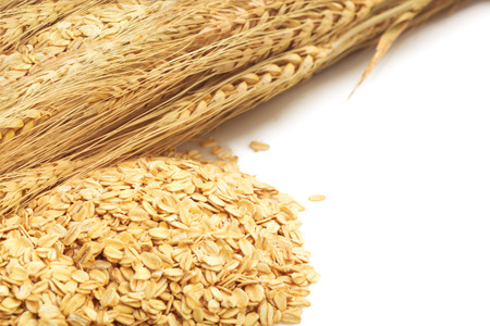 Close up of cereal grain whole rolled oats with copy space isolated on white background